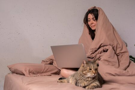 The concept of social distance and isolation. Work from home remotely over the Internet. A young woman works at home on a computer and a cat is next to her. Quarantine. Copy space. Banco de Imagens