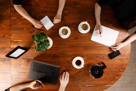 Group of business people working at desk,. Weekday work concept. Office stuff and gadgets nearby. Banco de Imagens