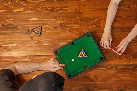 Young people play table billiards. Friendship and fun concept. Among friends and they are in a good mood. Top view.