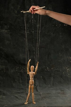 Puppet in the hands of puppeteer walks on isolated, background. Object on a texture background.