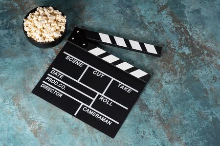 Clapper board with popcorn. Movie concept. Clapperboard on a textural background. Close-up.