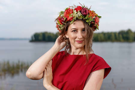 Slavic beauty with a flower wreath on her head in the lap of nature. Ancient pagan origin celebration concept. Summer solstice day. Mid summer.
