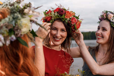 Lovely girls in flower wreaths in nature. Ancient pagan origin celebration concept. Summer solstice day. Mid summer.