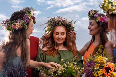 Lovely girls in flower wreaths in nature. Ancient pagan origin celebration concept. Summer solstice day. Mid summer. Banque d'images