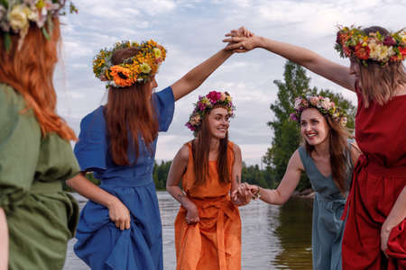Lovely girls in flower wreaths in nature. Ancient pagan origin celebration concept. Summer solstice day. Mid summer. Stock Photo