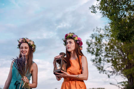 Two young and lovely girls in flower wreaths in nature. Ancient pagan origin celebration concept. Summer solstice day. Mid summer.
