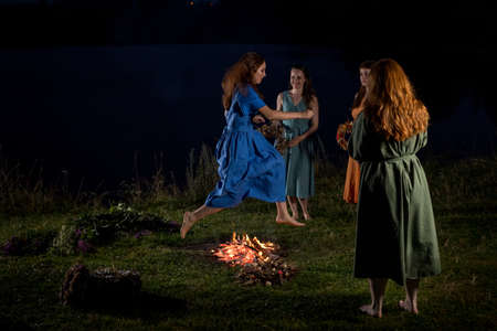 Lovely girls by the fire at night. Ancient pagan origin celebration concept. Night of Ivan Kupala.