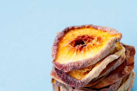 slices of dried peach on a blue background. dried fruits. eco. macro.