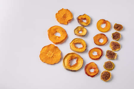 slices of dried persimmon, peach, plum and figs on a white background. dried fruits. eco. delicacy.