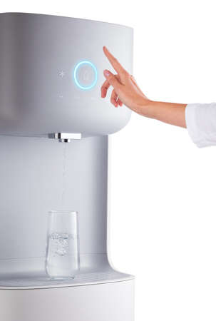 Modern technology concept. New water cooler format. Touch panel with a luminous indicator. A hand reaches for the cooler. Technological design. Close-up.