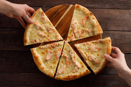 Appetizing pizza with salmon on a wooden background. Delicious food concept. 版權商用圖片