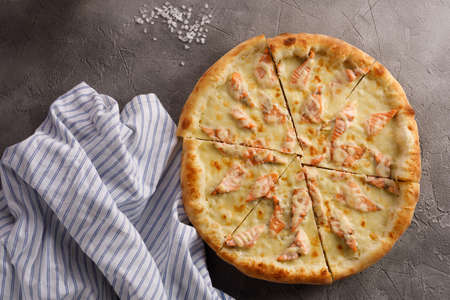 Appetizing pizza with salmon on a textured background. Delicious food concept. Archivio Fotografico
