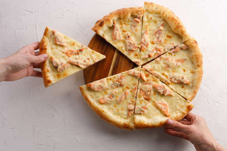 Appetizing pizza with salmon on a light textured background. Delicious food concept. 版權商用圖片
