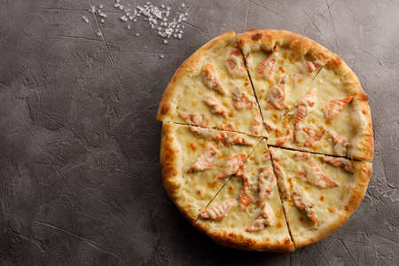 Appetizing pizza with salmon on a textured background. Delicious food concept. 版權商用圖片