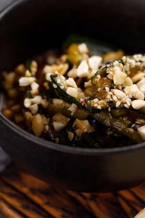 Broken cucumber salad with cashew nuts. Pan-Asian cuisine concept.