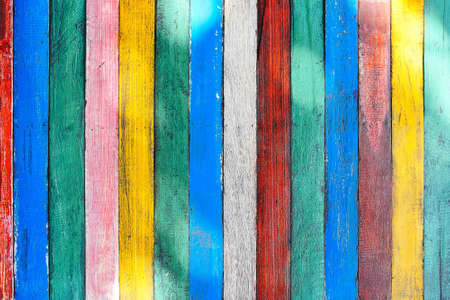 Mulricolored wooden table board surface background or wallpaper. Thin colorful vertical rough boards with knife marks