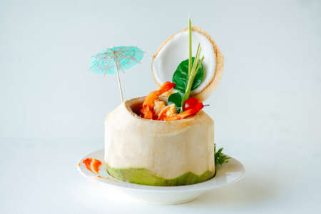 Cooked shrimps or prawns in red sauce in opened peeled coconut with herbs and cherry tomatoes. Side view. Tiny drink umbrella Stock fotó