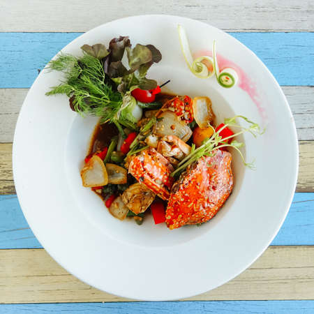 Fancy cooked crab with sauce with stewed onions, cherry tomatoes and herbs on a white plate. Top view, white and blue wooden surface Stock fotó