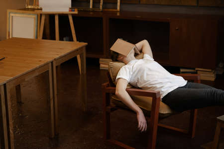 Girl in white t-shirt sleeps in dark cozy art class with book on face. Boring school lesson