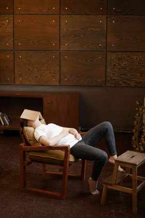 Girl in white t-shirt sleeps in dark cozy room with wooden walls with book on face. Boring school lesson