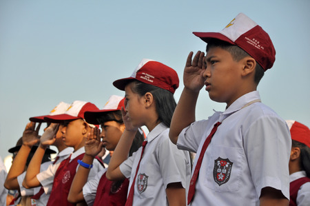 attempted: Indonesian elementary school students with red and white uniform saluted at ceremony of Independence Day of Indonesia in Jakarta, Indonesia.