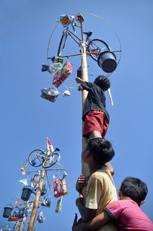celebratory event: Indonesian childs in teams try to climb to the top of a greased pole called a panjat pinang in order to get to the prizes tied to the top of pole. Cities and villages across Indonesia celebrated of Independence Day with traditional games, and music, and f