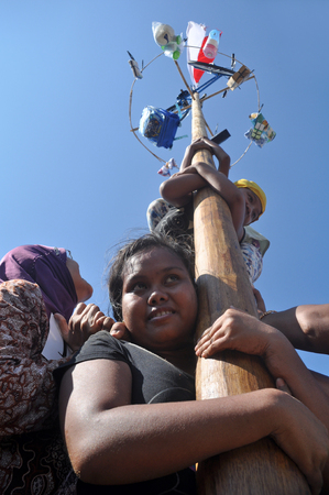 get across: Indonesian woman in teams try to climb to the top of a greased pole called a panjat pinang in order to get to the prizes tied to the top of pole. Cities and villages across Indonesia celebrated of Independence Day with traditional games, and music, and fl Editorial