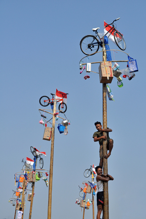get across: Indonesian men in teams try to climb to the top of a greased pole called a panjat pinang in order to get to the prizes tied to the top on August 17, 2014 in Jakarta, Indonesia. Cities and villages across Indonesia celebrated the countrys 70th anniversary