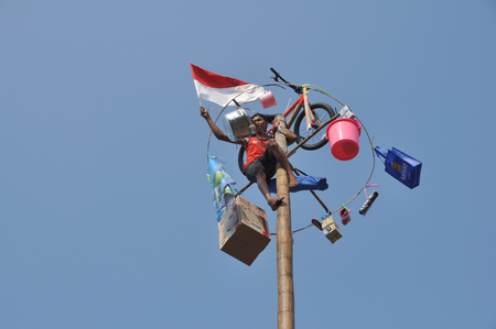 Indonesian men holding a flag on the top of a greased pole called a panjat pinang in order to get to the prizes tied to the top on August 17, 2014 in Jakarta, Indonesia. Cities and villages across Indonesia celebrated the countrys 70th anniversary of Ind
