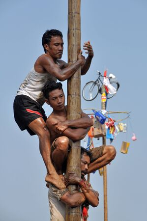 celebratory event: Indonesian men in teams try to climb to the top of a greased pole called a panjat pinang in order to get to the prizes tied to the top on August 17, 2014 in Jakarta, Indonesia. Cities and villages across Indonesia celebrated the countrys 70th anniversary