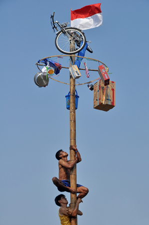 Indonesian men in teams try to climb to the top of a greased pole called a panjat pinang in order to get to the prizes tied to the top on August 17, 2014 in Jakarta, Indonesia. Cities and villages across Indonesia celebrated the country's 70th anniversary