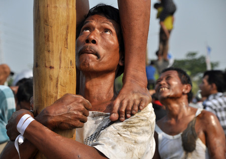 get across: Indonesian strong man was holding his friends leg in a climbing race attack nut trees in order to get to the prizes tied to the top on August 17, 2014 in Jakarta, Indonesia. Cities and villages across Indonesia celebrated the countrys 70th anniversary o