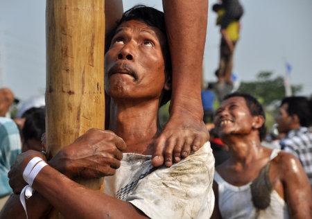 L'homme fort indonésien tenait la jambe de son ami dans une course d'escalade pour attaquer les arbres de noix afin d'obtenir les prix liés au sommet le 17 août 2014 à Jakarta, en Indonésie. Les villes et villages d'Indonésie ont célébré le 70e anniversaire du pays