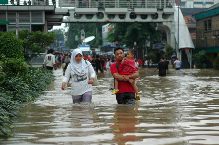 kampung: Jakarta resident walk across the flooding street in Kampung Melayu, Jakarta, Indonesia. Editorial