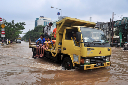 kampung: Jakarta resident across the flooding street on vehicle in Kampung Melayu, Jakarta, Indonesia.