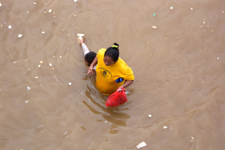 kampung: A mother with a child crossing flooded roads caused by heavy rains and overflowing rivers in Kampung Melayu, Jakarta, Indonesia. Editorial