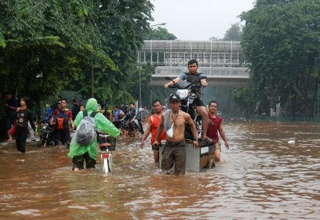 kampung: Jakarta resident across the flooding street with using a wooden cart in Kampung Melayu, Jakarta, Indonesia.