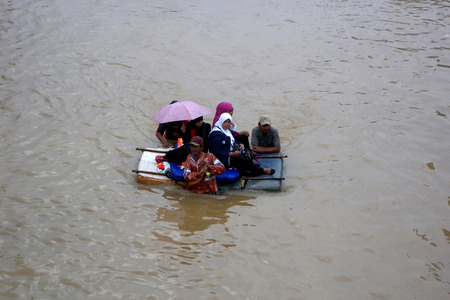 kampung: Jakarta resident across the flooding street with artificial boat in Kampung Melayu, Jakarta, Indonesia.