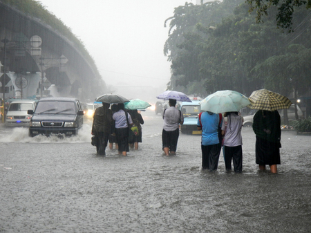 Jakarta resident across the flooding street in Central Jakarta, Indonesia. Flooding in Jakarta caused by heavy rains and overflowing rivers