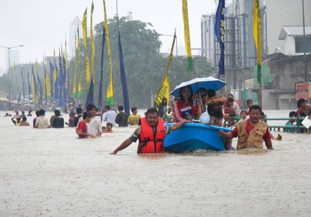 kampung: Jakarta resident across the flooding street in Kampung Melayu, Jakarta, Indonesia. Editorial