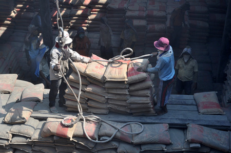 unload: Indonesian port workers unload a ship with a cement bags cargo in a traditional way in Sunda Kelapa port on March 22 in Jakarta 2015, Indonesia. Editorial