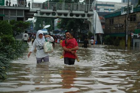 Jakarta, Indonesia - January 19, 2014 : Jakarta resident walk across the flooding street in Kampung Melayu, Jakarta, Indonesia.
