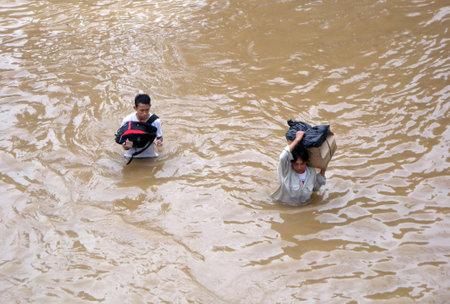 kampung: Jakarta, Indonesia - January 18, 2014 : Jakarta resident across the flooding street in Kampung Melayu, Jakarta, Indonesia, 19 January 2014.