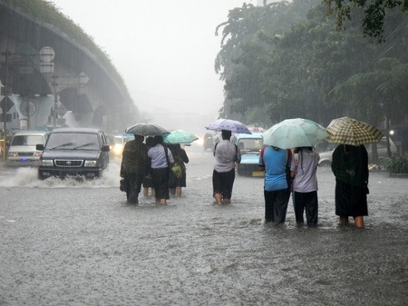Jakarta, Indonesia - January 17, 2013 : Jakarta resident across the flooding street in Central Jakarta, Indonesia. Flooding in Jakarta caused by heavy rains and overflowing rivers