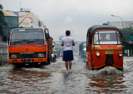 Jakarta, Indonesia - January 17, 2013 : Vehicles break through the flood that flooded several roads in Jakarta, Indonesia