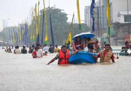 kampung: Jakarta, Indonesia - January 18, 2014 : Jakarta resident across the flooding street in Kampung Melayu, Jakarta, Indonesia.