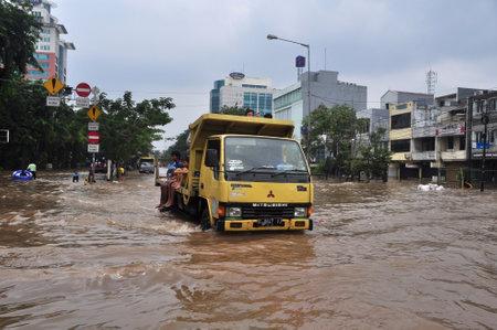kampung: Jakarta, Indonesia - February 4, 2014 : Jakarta resident across the flooding street on vehicle in Kampung Melayu, Jakarta, Indonesia. Editorial