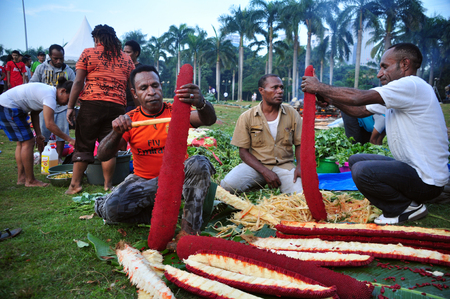 Jakarta, Indonesia - May 25, 2014 : Papua people peeling red fruit at the festival Papua in Monas, Jakarta Editorial
