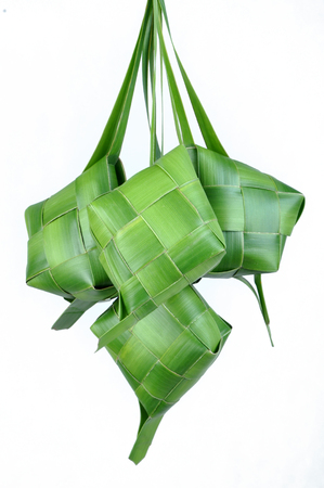 Ketupat, a type of dumpling made from rice packed inside a diamond-shaped container of woven palm leaf pouch. commonly found in Indonesia, Malaysia, Brunei, Singapore, and the Philippines. Stock Photo