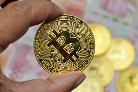 Holding bitcoin with indonesia money hundred thousand rupiah background